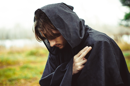 a monk in a black robe praying in the woods on his knees 写真素材
