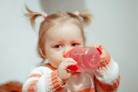 Cute little girl drinking water in summer