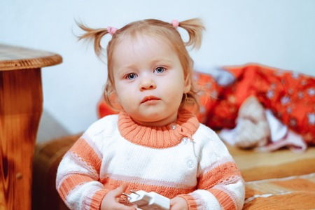 a little girl in a blouse with tails is at home