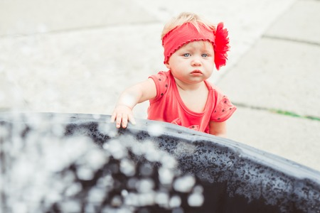 Cute baby girl drinking from water drinking fountain in summer