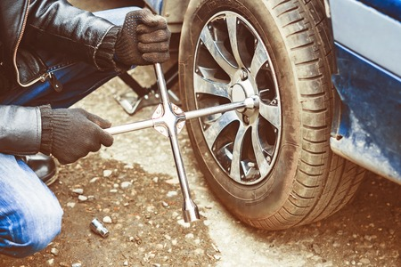 Change a flat car tire on road with Tire maintenance, damaged car tyre Foto de archivo