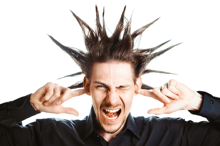 A young man with a Mohawk on his head covers his ears Stock Photo