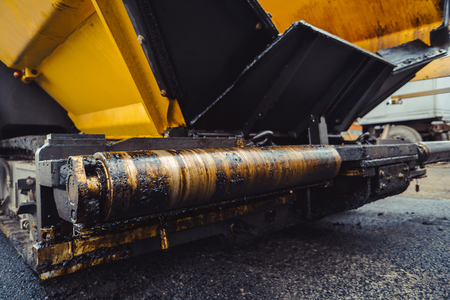 Road construction works with roller compactor machine and asphalt finisher Stock Photo