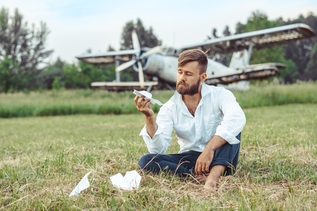a man on the background of an old plane lets paper airplanes sitting on the grass