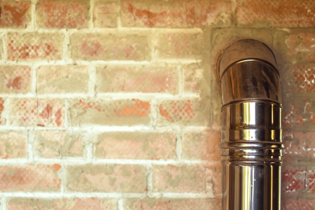 iron pipe of the fireplace of the house in a brick wall Banque d'images