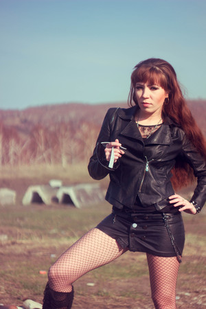 beautiful girl in leather jacket on the field