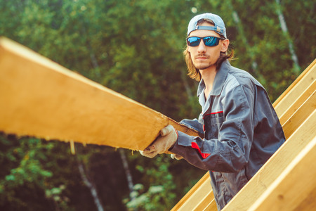 worker roofer builder working on roof structure on construction site Stock Photo