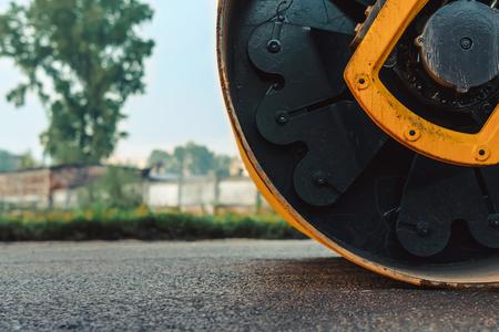 道路建設はローラーコンパクターマシンとアスファルトフィニッシャーで動作します 写真素材