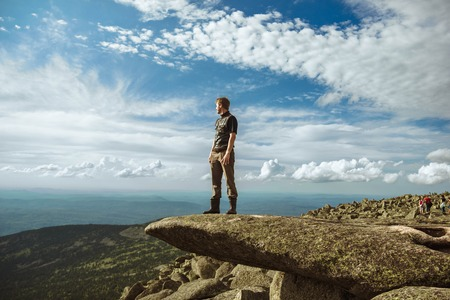A man stands on a mountain hill and contemplates the landscape over the mountains.