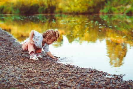 a little girl standing on the river Bank 版權商用圖片