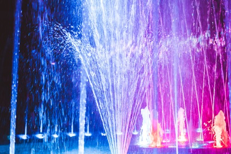 Colored water fountain at night Stock Photo