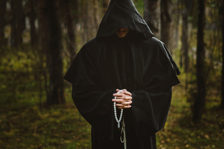 A creepy man in a black hood in the forest 免版税图像