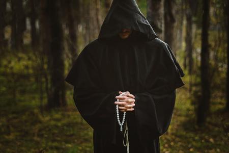 Un hombre espeluznante con una capucha negra en el bosque.