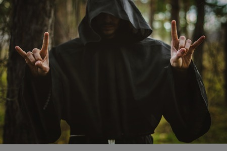 A creepy man in a black hood in the forest Banco de Imagens