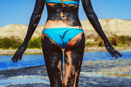girl in a swimsuit smeared in mud
