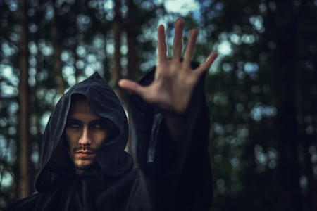 the black monk pointing his finger in the woods Stock fotó