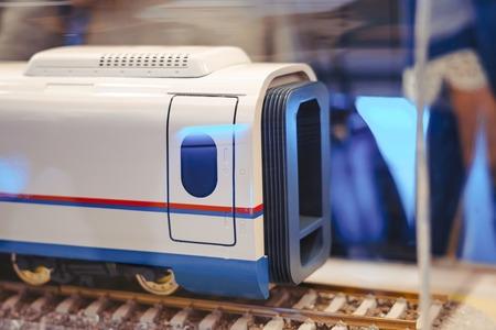 Miniature toy model of modern train crossing bridge