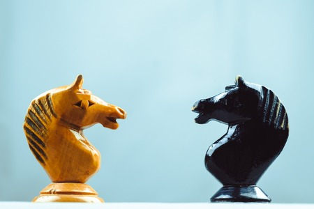 Chess knights face to face on grey background