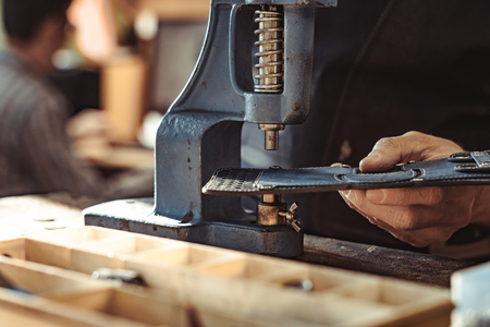 Man works in carpentry workshop. He fixes wooden handle in vice. Different tools are on workbench. Men at work. Hand work.