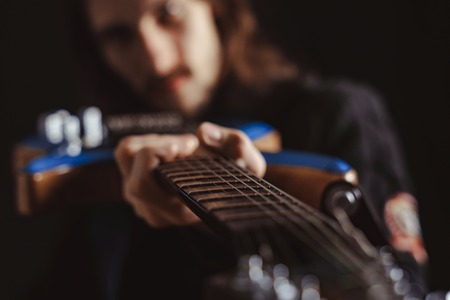 the guy holds the guitar focus on the fretboard