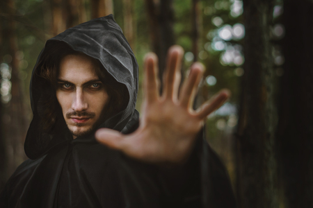 the black monk pointing his finger in the woods Imagens
