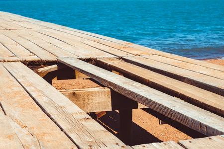 old wooden pier by the sea broken boards Фото со стока