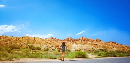 background girl standing turned her back on the city asphalt road among the mountains Stock fotó
