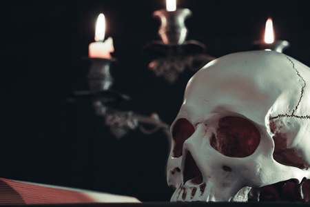 Candle lighting of Skull with candle and books on wooden desk decorate for Halloween Theme with copy space. Still Life image and selective focus