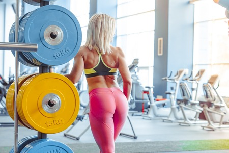 Beautiful blonde is standing in the gym