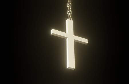Golden 3D Christian cross on a chain hanging in the dark
