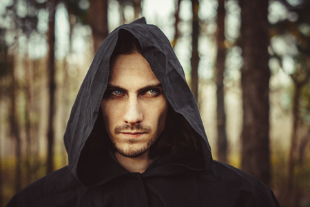 A creepy man in a black hood in the forest Imagens
