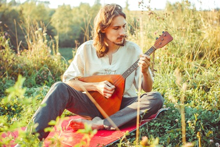 a man plays a balalaika sitting on the grass in the forest