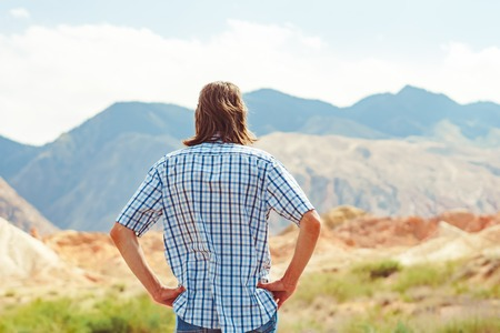the guy in the shirt is on the road at the foot of the mountains Stockfoto