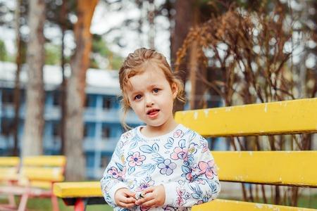 little girl joyful on the street sitting on a bench