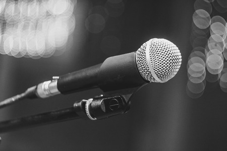 microphone on the stand in the concert hall, burning lights on the background