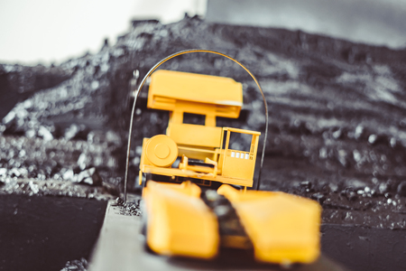 toy yellow tractor in the scenery of coal mining