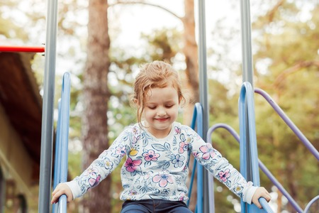 a child plays on the Playground riding a slide Stockfoto