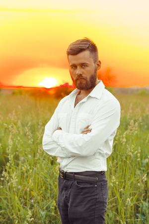 Beautiful long-bearded man at sunset in the open field