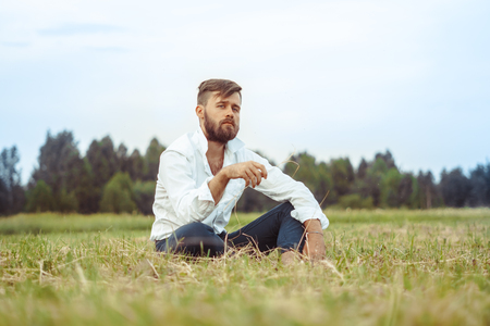 the guy with the beard is sitting on the grass with a serious expression Imagens - 124706950