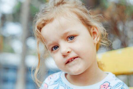 kleines Mädchen fröhlich auf der Straße sitzend auf einer Bank