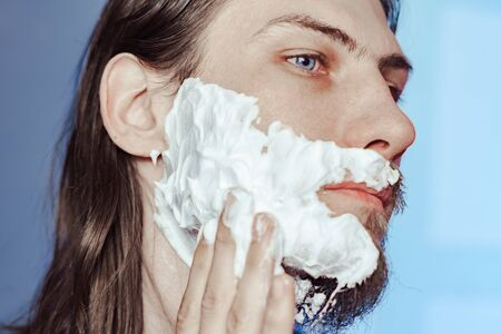 the guy puts shaving cream on the face with long hair