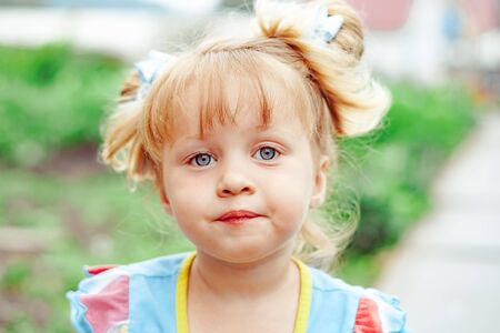 Close-up portrait of attractive little girl outdoors