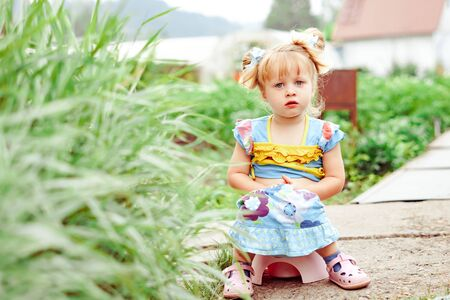 portrait of cute Happy little girl sitting on potty outdoors Stock Photo