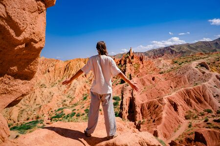 Successful male tourist standing on top of the mountain, above the red canyon