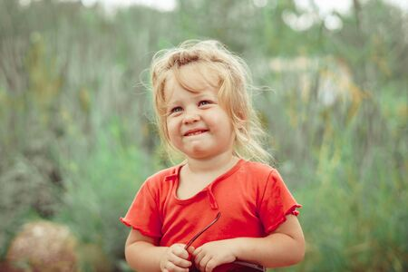 portrait of a happy little girl outdoors in a red shirt Stockfoto - 130099253