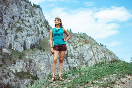 woman traveler with backpack looking at amazing mountains and river, concept of traveling wandering lust, space for text, atmospheric epic moment