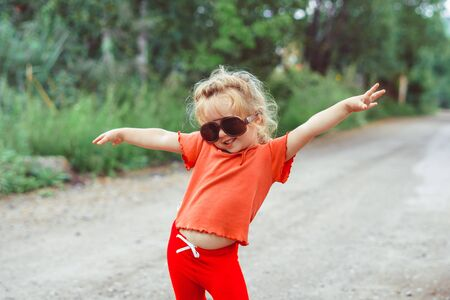 little girl dancing in glasses outdoors 写真素材