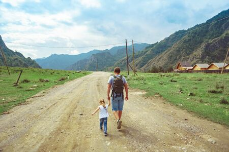father and daughter go camping on the road near the mountains