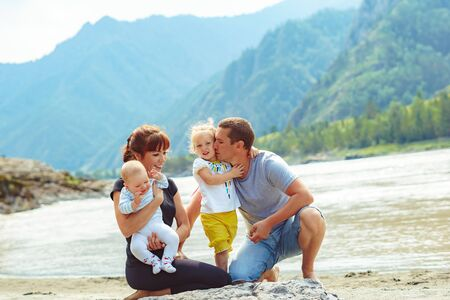 family with two children on the river Bank against the mountains