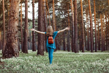 a young girl walks through the pine forest